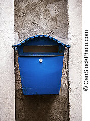 Old blue mailbox mounted on a wall