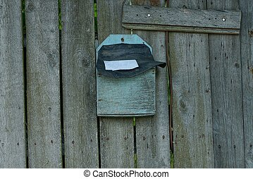 old blue plywood mailbox hanging on gray wooden planks