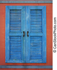 old blue window on red wall