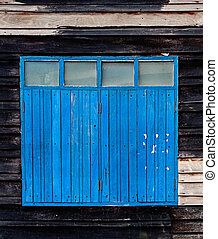 Old Blue Window on Weathered Wooden Wall