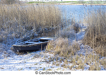 Old boat among reeds on the bank of a frozen river