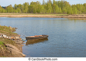 Old boat by the river on a leash