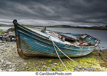 Old boat on beach - Weathered fishing boat lying on a rocky...