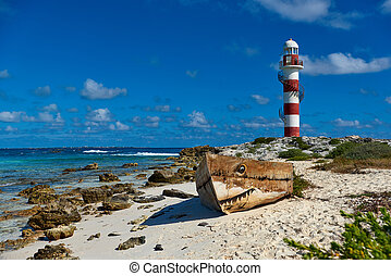 Old boat on the beach and lighthouse