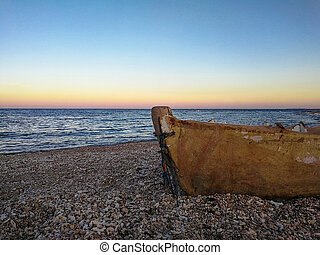 Old boat on the beach at sunset