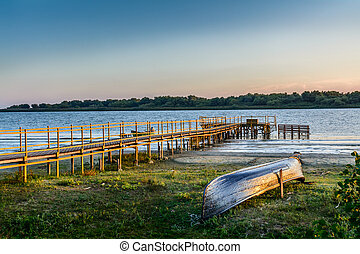 Old boat on the coast near the wharf. Rustic landscape with wooden dock in the summer evening