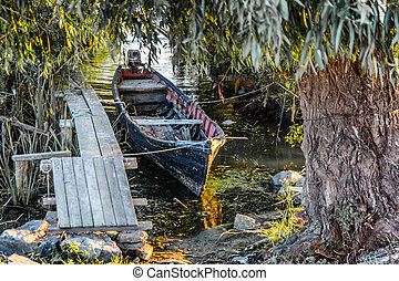 Old boat on the dock among the trees. Rustic landscape with wooden pier in the summer sunset.