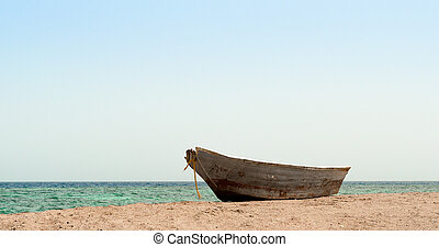 old boat on the sand against the Red sea in Egypt