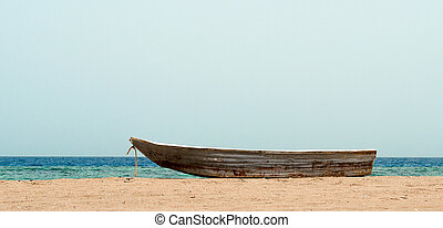 old boat on the sand against the sea