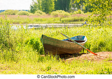 old boat on the shore of a beautiful lake on a sunny day