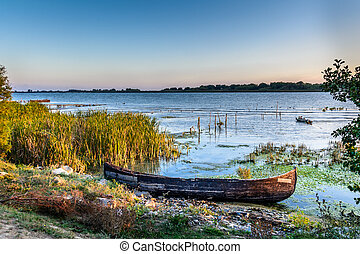 Old boat on the water in the lake among the reeds. Bright and calm view with wooden boat on the coast in the summer .