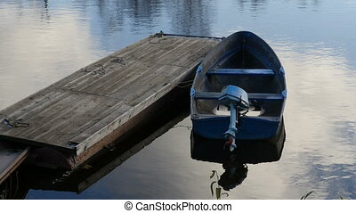 Old boat with an outboard motor moored at the pontoon