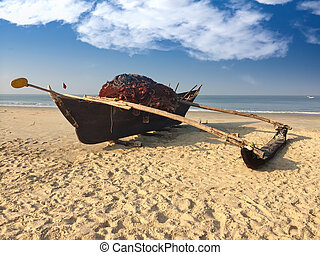 Old boat with fishing net on a sandy beach. India. Goa.