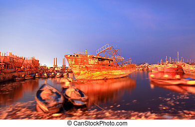 Old boats in the fishing harbor Visakhapatnam, India with long exposure