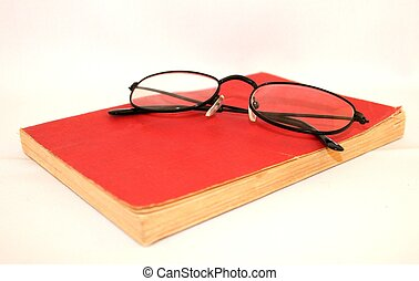 A pair of glasses on top of an old book