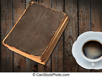 old book and a cup of coffee on wood background