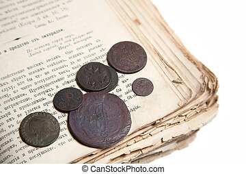 Old coins and age-old book isolated on a white background