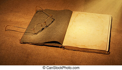 old book and glasses in ambient light