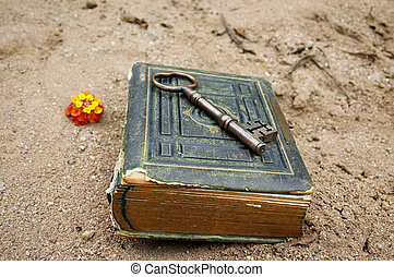 book and key - old book and key on sand or beach