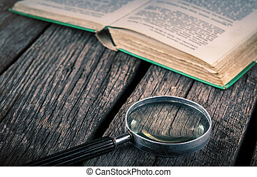 old book and magnifying glass on vintage wood