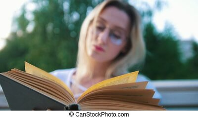 Old book in front of attractive girl student reading in the park