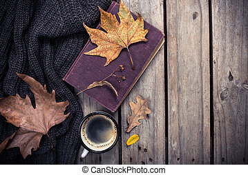 Old book, knitted sweater with autumn leaves and coffee mug