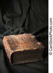 Old book on black background. Ancient christian Bible. Antique Holy Scripture book. Cross on bible cover.
