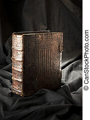 Old book on black background. Ancient christian Bible. Antique Holy Scripture book. Strap on book side.