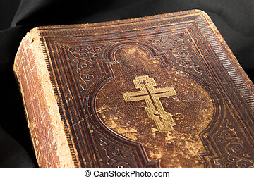 Old book on black background. Ancient christian Bible. Close up antique Holy Scripture book. Cross on bible cover.