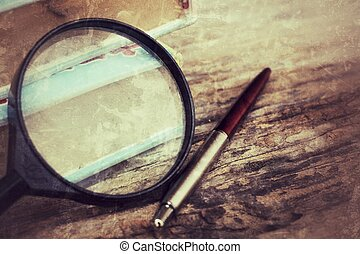 Old book , pen and magnifying glass