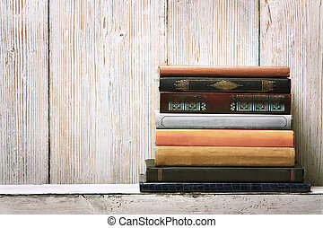 old book shelf blank spines, empty binding stack on wood texture background, knowledge concept