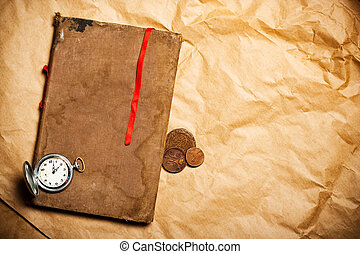 old book with red bookmark and antique watch and coins on yellow paper