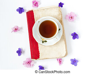 Old book with tea or coffee with flowers on white background .