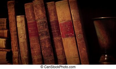 Old books - Ancient books in a bookshelf. Pan from right to ...