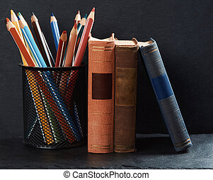 Old books and pencils on a bookshelf