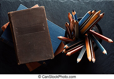 Old books and pencils. Top view