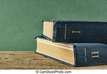 Old books on a wooden shelf against a green wall