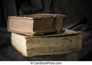 Old books on black background. Ancient christian Bible. Antique Holy Scripture books. Pile of books with page sides.