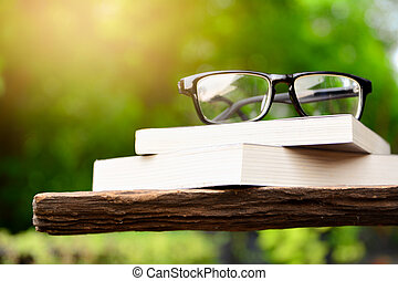 Old books with glasses on a wooden table.