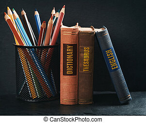 old books with pencils on stone shelf