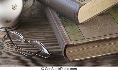Old books with reading glasses on a wooden table