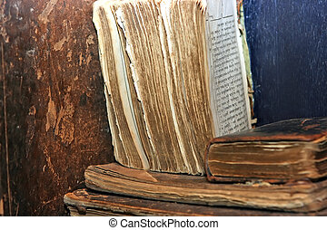 Old books with torn edges lying on the dusty shelf