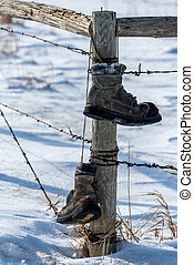 Old boots hanging from fence post in the snow in Saskatchewan, Canada
