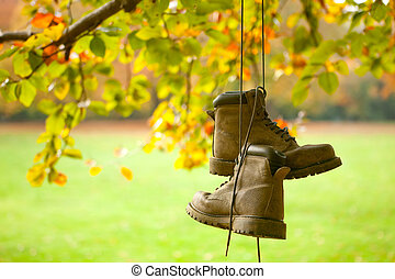 Old boots in autumn - Old worn boots hanging on a tree in an...