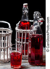 Old bottles in basket with red juice