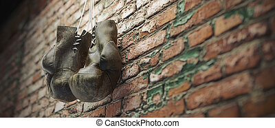 Old boxing gloves hang on nail on brick wall with copy space for text. High resolution 3d render