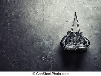 old boxing gloves hang on nail on texture wall with copy...