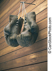 Old boxing gloves hang on nail on wooden wall with copy space for text. High resolution 3d render