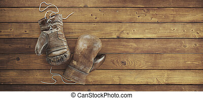 Old boxing gloves lie on the wooden surface with copy space for text. High resolution 3d render