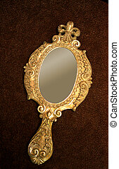 Old decorated hand-held mirror on brown surface